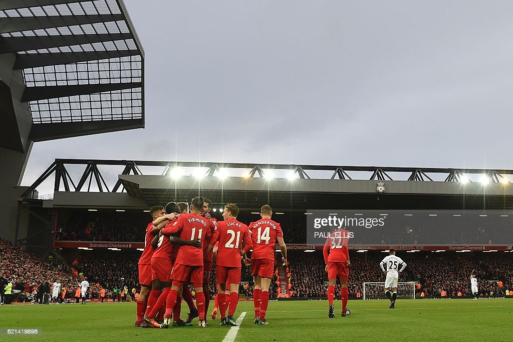 Liverpool players mob Liverpool's Senegalese midfielder Sadio Mane (2L) after he scored the team's fifth goal during the English Premier League football match between Liverpool and Watford at Anfield in Liverpool, north west England on November 6, 2016. / AFP / PAUL ELLIS / RESTRICTED TO EDITORIAL USE. No use with unauthorized audio, video, data, fixture lists, club/league logos or 'live' services. Online in-match use limited to 75 images, no video emulation. No use in betting, games or single club/league/player publications. /