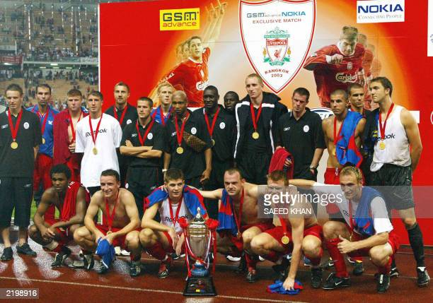 Liverpool players pose for a photgraph with the winning trophy during the awards ceremony after defeating Thailand in Bangkok 24 July 2003 during the...