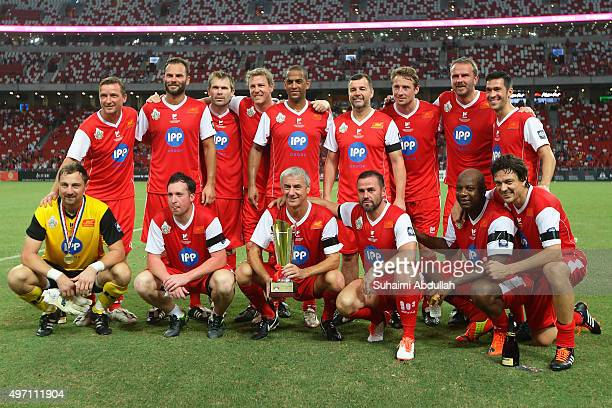 Liverpool players pose with the trophy after defeating Manchester United during The Castlewood Group Battle Of The Reds 2015 at National Stadium on...