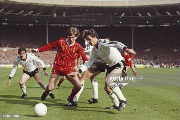 Liverpool striker Kenny Dalglish challenges Kevin Moran of Manchester United as Arthur Albiston looks on during the 1983 League Cup Final at Wembley...