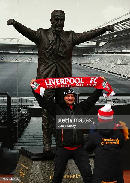 Liverpool supporter has his picture taken at the Bill Shankly statue prior to the Barclays Premier League match between Liverpool and Swansea City at...