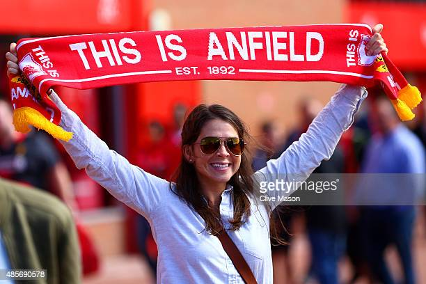 Liverpool supporter poses for photographs outside the stadium prior to the Barclays Premier League match between Liverpool and West Ham United at...