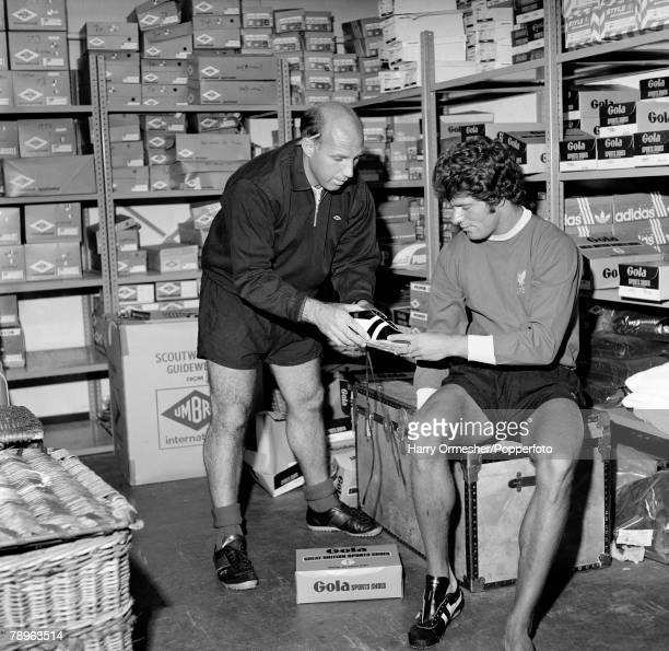 Liverpool FC Assistant Manager Ronnie Moran sorts out some training shoes for Phil Boersma pictured in the boot room at Anfield 10th July 1975