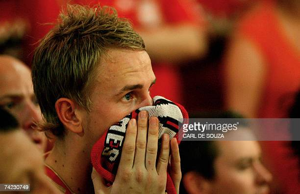 A Liverpool Football Club fan watches television at a pub in Liverpool as his team concede a goal to AC Milan during their 2007 Champions League...