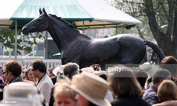 Racegoers mingle around the Red Rum statue on 'Ladies Day' at Aintree Racecourse in Liverpool northwest England 13 April 2007 during the second day...