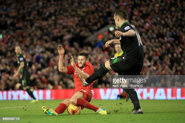 Liverpool's Adam Lallana and Stoke City's Charlie Adam battle for the ball