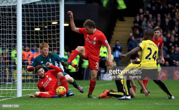 Liverpool's Adam Lallana scrambles the ball clear from in front of his goal