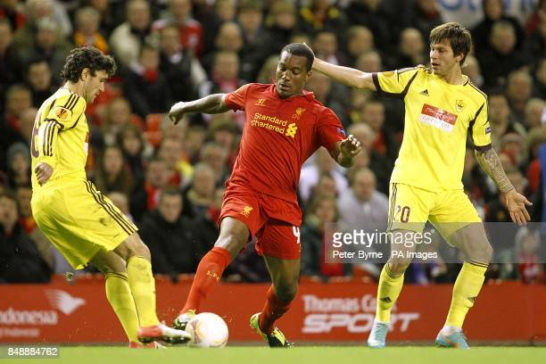 Liverpool's Andre Wisdom battles for the ball with Anzhi Makhachkala's Fedor Smolov and Yury Zhirkov