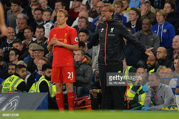 Liverpool's Brazilian midfielder Lucas Leiva stands alongside Liverpool's German manager Jurgen Klopp as Klopp shouts instructions to his players...
