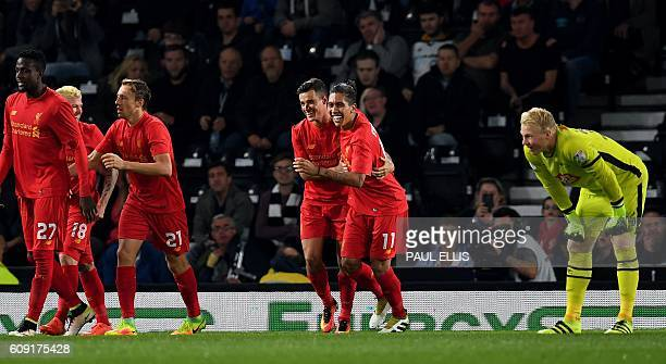 Liverpool's Brazilian midfielder Philippe Coutinho celebrates after scoring their second goal with teammate Roberto Firmino as Derby's English...