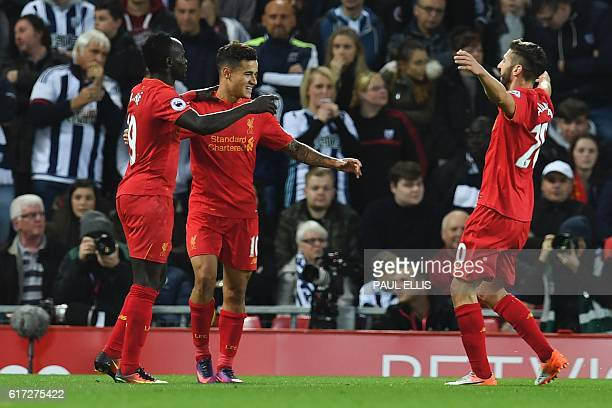 Liverpool's Brazilian midfielder Philippe Coutinho celebrates scoring their second goal with Liverpool's Senegalese midfielder Sadio Mane and...
