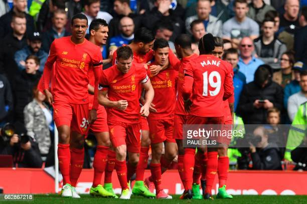 Liverpool's Brazilian midfielder Philippe Coutinho celebrates with teammates after scoring their second goal during the English Premier League...