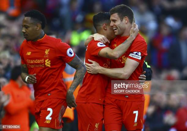 Liverpool's Brazilian midfielder Philippe Coutinho celebrates with Liverpool's English midfielder James Milner after scoring during the English...