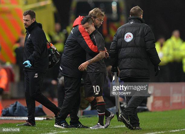 Liverpool's Brazilian midfielder Philippe Coutinho gets a hug from Liverpool's German manager Jurgen Klopp as Coutinho leaves the field early in the...