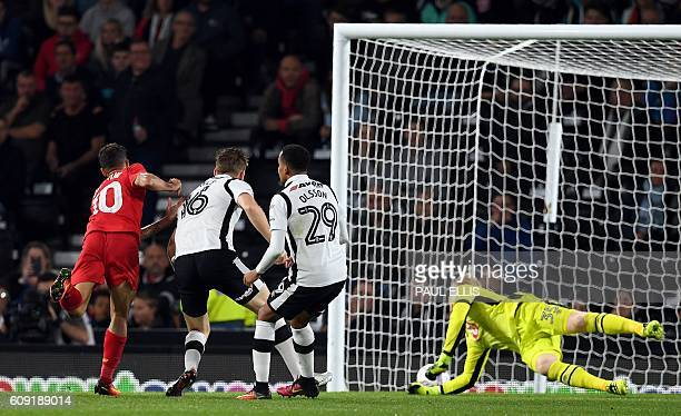 Liverpool's Brazilian midfielder Philippe Coutinho scores their second goal as Derby's English goalkeeper Jonathan Mitchell dives across his goal...