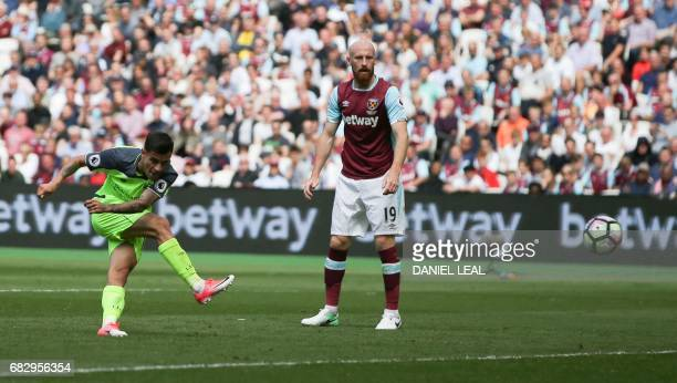 Liverpool's Brazilian midfielder Philippe Coutinho scores their third goal as West Ham United's Welsh defender James Collins looks on during the...