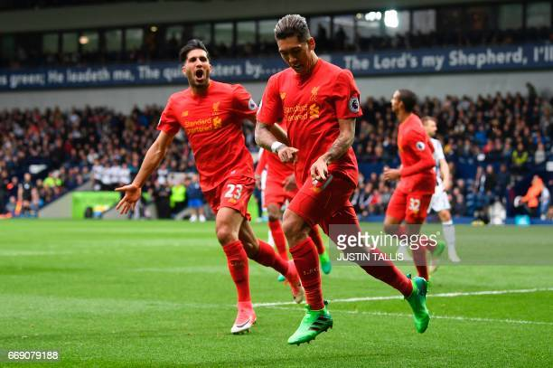 Liverpool's Brazilian midfielder Roberto Firmino celebrates scoring the opening goal with Liverpool's German midfielder Emre Can during the English...