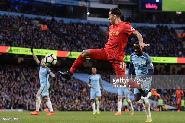 Liverpool's Brazilian midfielder Roberto Firmino crosses the ball during the English Premier League football match between Manchester City and...