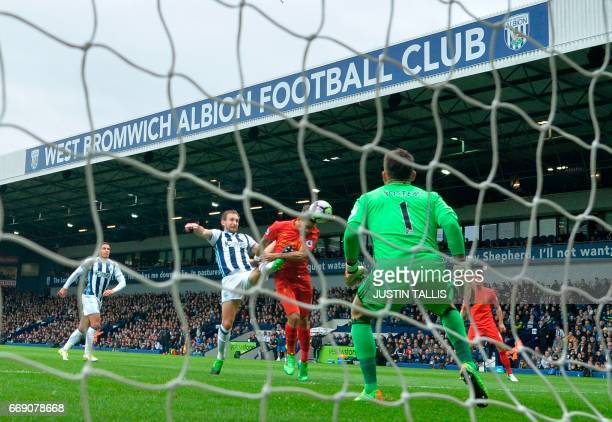 Liverpool's Brazilian midfielder Roberto Firmino heads the opening goal past West Bromwich Albion's English defender Craig Dawson as West Bromwich...
