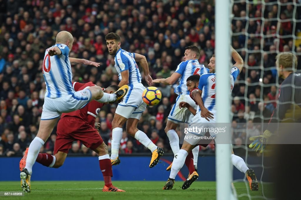 Liverpool's Brazilian midfielder Roberto Firmino (2nd L) scores their second goal with this header during the English Premier League football match between Liverpool and Huddersfield Town at Anfield in Liverpool, north west England on October 28, 2017. / AFP PHOTO / Paul ELLIS / RESTRICTED TO EDITORIAL USE. No use with unauthorized audio, video, data, fixture lists, club/league logos or 'live' services. Online in-match use limited to 75 images, no video emulation. No use in betting, games or single club/league/player publications. /