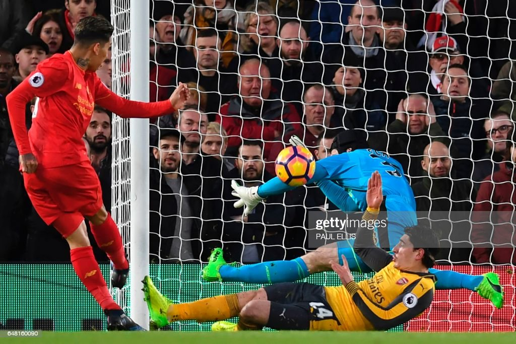 Liverpool's Brazilian midfielder Roberto Firmino (L) shoots past Arsenal's Czech goalkeeper Petr Cech to score the opening goal of the English Premier League football match between Liverpool and Arsenal at Anfield in Liverpool, north west England on March 4, 2017. / AFP PHOTO / Paul ELLIS / RESTRICTED TO EDITORIAL USE. No use with unauthorized audio, video, data, fixture lists, club/league logos or 'live' services. Online in-match use limited to 75 images, no video emulation. No use in betting, games or single club/league/player publications. /