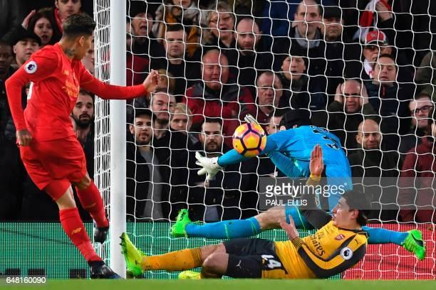 Liverpool's Brazilian midfielder Roberto Firmino shoots past Arsenal's Czech goalkeeper Petr Cech to score the opening goal of the English Premier...