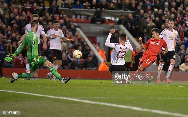Liverpool's Brazilian midfielder Roberto Firmino shoots past Manchester United's Spanish goalkeeper David de Gea to score his team's second goal...