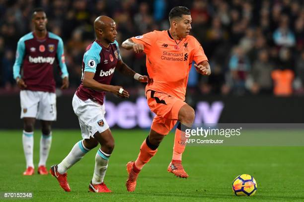 Liverpool's Brazilian midfielder Roberto Firmino vies with West Ham United's Frenchborn Ghanaian midfielder Andre Ayew during the English Premier...