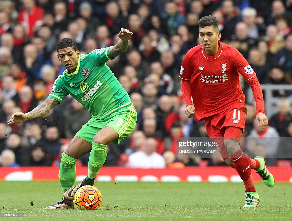 Liverpool's Brazilian striker Roberto Firmino (R) vies with Sunderland's Dutch defender Patrick van Aanholt during the English Premier League football match between Liverpool and Sunderland at Anfield in Liverpool, northwest England, on February 6, 2016. / AFP / LINDSEY PARNABY / RESTRICTED TO EDITORIAL USE. No use with unauthorized audio, video, data, fixture lists, club/league logos or 'live' services. Online in-match use limited to 75 images, no video emulation. No use in betting, games or single club/league/player publications. /