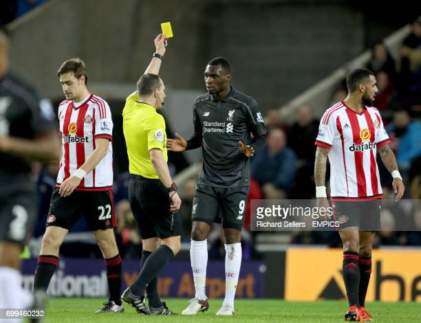 Liverpool's Christian Benteke is booked by referee Kevin Friend