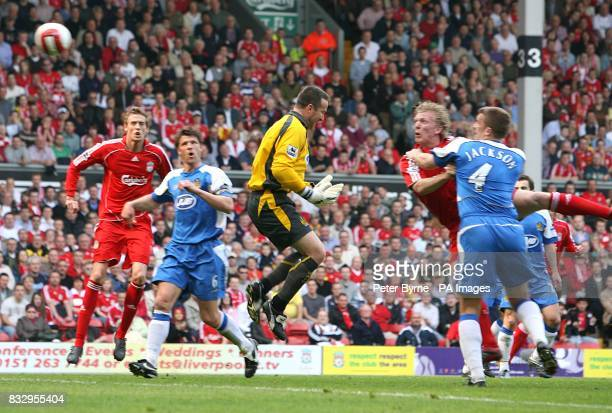 Liverpool's Dirk Kuyt heads home the opening goal of the match