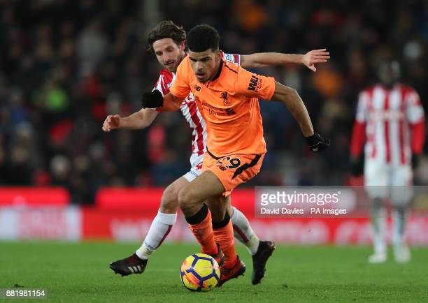 Liverpool's Dominic Solanke is challenged by Stoke City's Joe Allen during the Premier League match at the bet365 Stadium Stoke