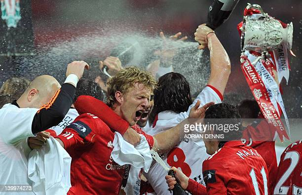 Liverpool's Dutch footballer Dirk Kuyt is doused in champagne as his team celebrate beating Cardiff City in a penalty shoot out in the League Cup...