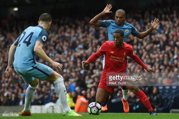 Liverpool's Dutch midfielder Georginio Wijnaldum vies with Manchester City's English defender John Stones during the English Premier League football...