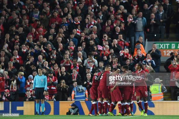 Liverpool's Egyptian midfielder Mohamed Salah celebrates with teammates after scoring during the UEFA Champions League Group E football match between...