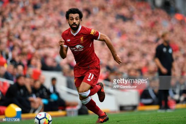 Liverpool's Egyptian midfielder Mohamed Salah runs with the ball during the English Premier League football match between Liverpool and Manchester...