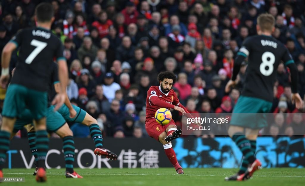 TOPSHOT - Liverpool's Egyptian midfielder Mohamed Salah scores the opening goal during the English Premier League football match between Liverpool and Southampton at Anfield in Liverpool, north west England on November 18, 2017. / AFP PHOTO / Paul ELLIS / RESTRICTED TO EDITORIAL USE. No use with unauthorized audio, video, data, fixture lists, club/league logos or 'live' services. Online in-match use limited to 75 images, no video emulation. No use in betting, games or single club/league/player publications. /