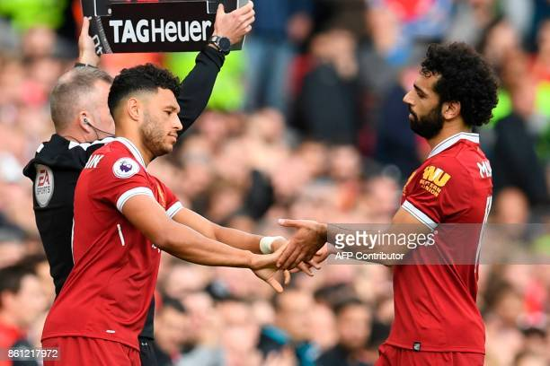 Liverpool's Egyptian midfielder Mohamed Salah shakes hands with Liverpool's English midfielder Alex OxladeChamberlain as he is substituted during the...