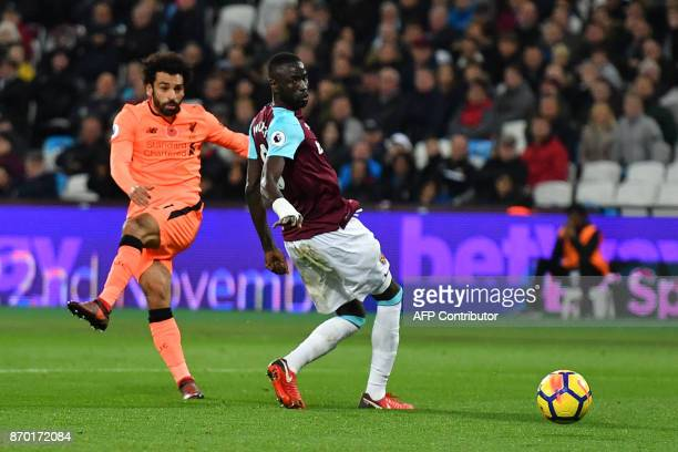 Liverpool's Egyptian midfielder Mohamed Salah shoots past West Ham United's Senegalese midfielder Cheikhou Kouyate to score their fourth goal during...