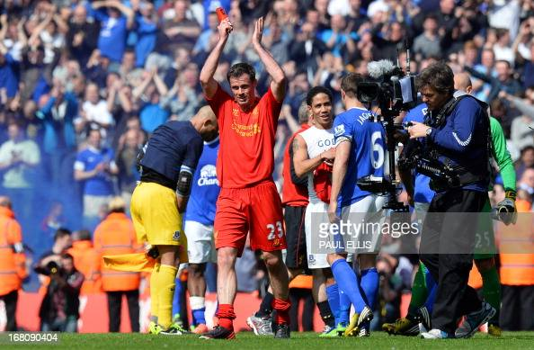 Liverpool's English defender Jamie Carragher applauds the crowd after his final derby match before retiring after the English Premier League football...