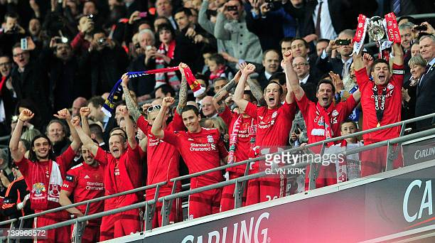 Liverpool's English footballer Steven Gerrard leads his team in holding up the trophy after beating Cardiff City in the League Cup Final at Wembley...