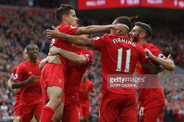 Liverpool's English midfielder Adam Lallana is congratelated by teammates after scoring his team's first goal during the English Premier League...