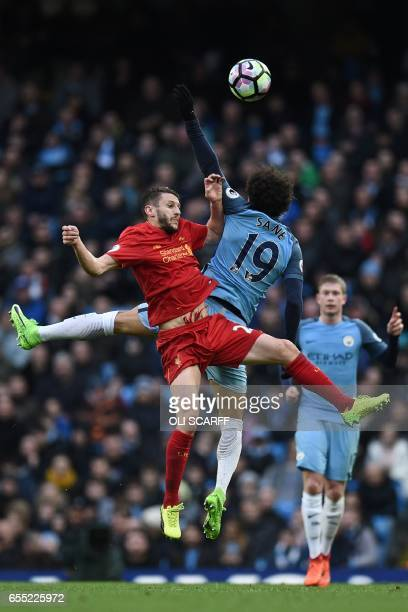 Liverpool's English midfielder Adam Lallana vies with Manchester City's German midfielder Leroy Sane during the English Premier League football match...