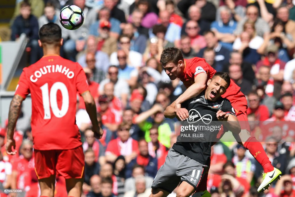 Liverpool's English midfielder James Milner (top) heads the ball over Southampton's Serbian midfielder Dusan Tadic during the English Premier League football match between Liverpool and Southampton at Anfield in Liverpool, north west England on May 7, 2017. / AFP PHOTO / Paul ELLIS / RESTRICTED TO EDITORIAL USE. No use with unauthorized audio, video, data, fixture lists, club/league logos or 'live' services. Online in-match use limited to 75 images, no video emulation. No use in betting, games or single club/league/player publications. /
