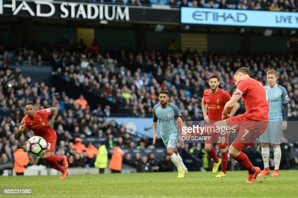 Liverpool's English midfielder James Milner scores the opening goal from the penalty spot during the English Premier League football match between...