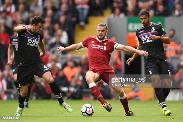 Liverpool's English midfielder Jordan Henderson vies with Crystal Palace's Serbian midfielder Luka Milivojevic and Crystal Palace's English...