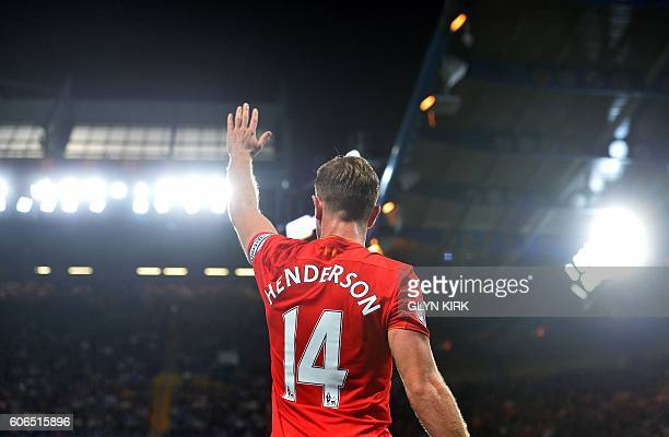 Liverpool's English midfielder Jordan Henderson waves to the fans following the English Premier League football match between Chelsea and Liverpool...