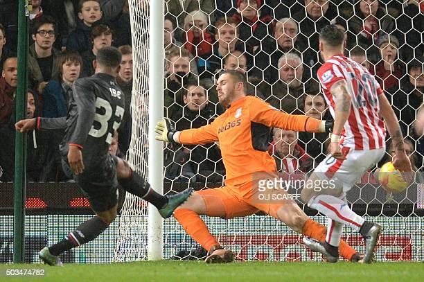 Liverpool's English midfielder Jordon Ibe strikes the ball past Stoke City's English goalkeeper Jack Butland to score the opening goal during the...