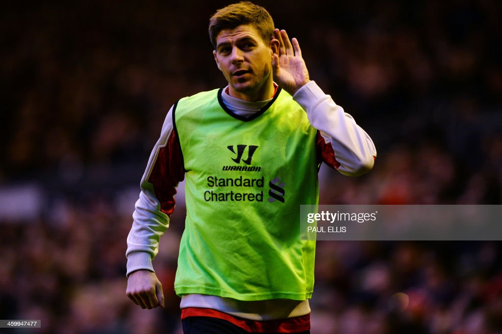 Liverpool's English midfielder Steven Gerrard gestures to Hull City supporters as he warms up during the English Premier League football match between Liverpool and Hull City at Anfield in Liverpool, northwest England, on January 1, 2014. USE. No use with unauthorized audio, video, data, fixture lists, club/league logos or live services. Online in-match use limited to 45 images, no video emulation. No use in betting, games or single club/league/player publications.
