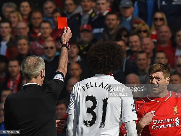 Liverpool's English midfielder Steven Gerrard is shown a red card by referee Martin Atkinson in the first minute of the second half after coming on...